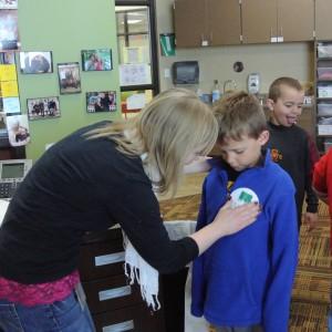 First grade teacher puts sticker on student